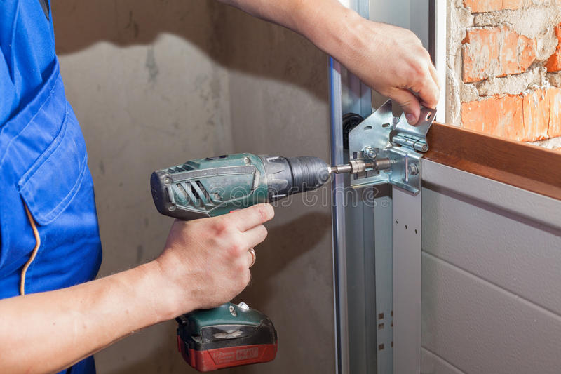 Garage doors installation.Worker installing lifting system in metal profil with screwdriver. royalty free stock images