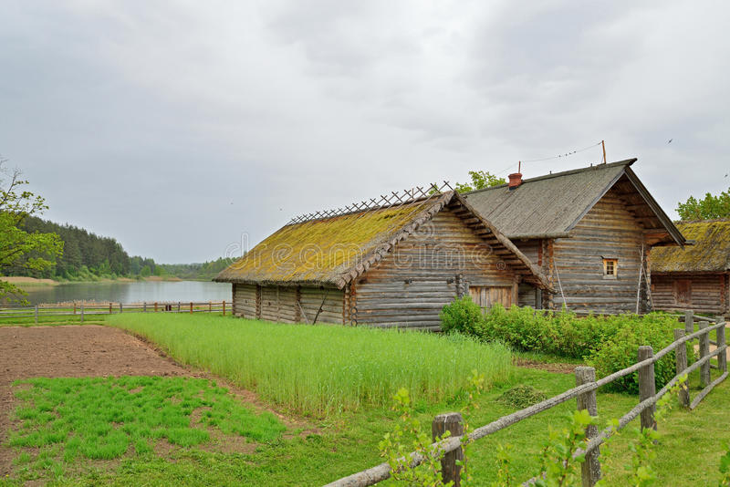The garden and the old Russian log hut in Pushkin Mikhailovskoe. Summer cloudy day royalty free stock photo