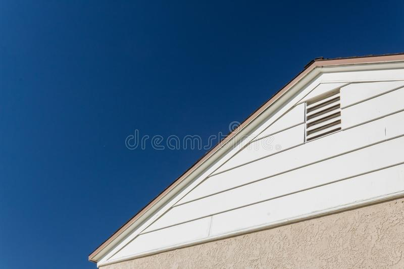 Generic house view of side and roof edge, stucco and vinyl with attic ventilation set against a deep blue sky stock image