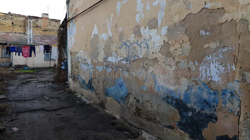 Old rough stone wall surface of ruined building with dirty flaking plaster. Ghetto court yard with hanging laundry clothes and weathered wall on foreground royalty free stock image