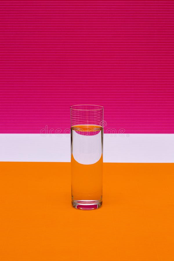 Glass with a glass of liquid on a colored royalty free stock photo