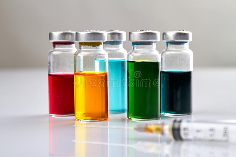 Glass vials with colored medicine liquid and syringe. royalty free stock image