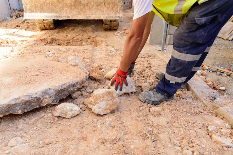 Gloved worker removes a rock from the road on a construction site stock images