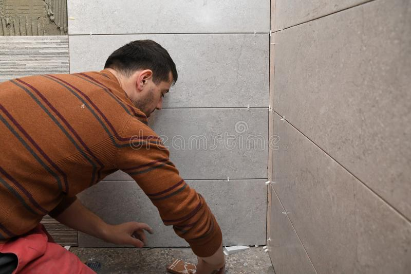 Gluing tiles on the wall. Laying tiles on the wall stock image