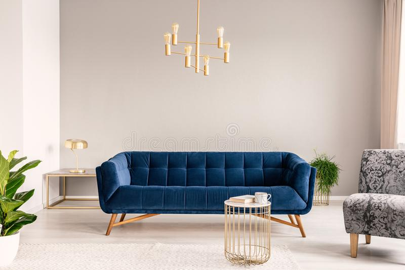 Gold lamp hanging above royal blue sofa in real photo of light grey sitting room interior with empty wall. Concept royalty free stock images