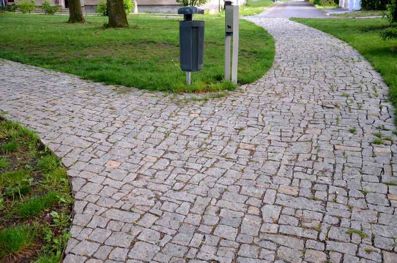 Granite paving of irregular sections of chipped stone around a park with green lawn gray color of the pedestrian path. Stone, road, garden, street, cobblestone stock photography
