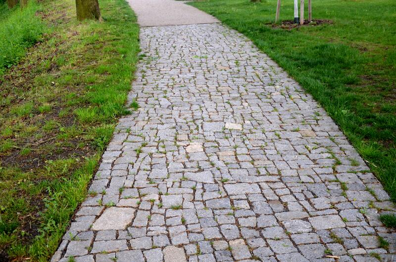 Granite paving of irregular sections of chipped stone around a park with green lawn gray color of the pedestrian path. Stone, road, garden, street, cobblestone stock image