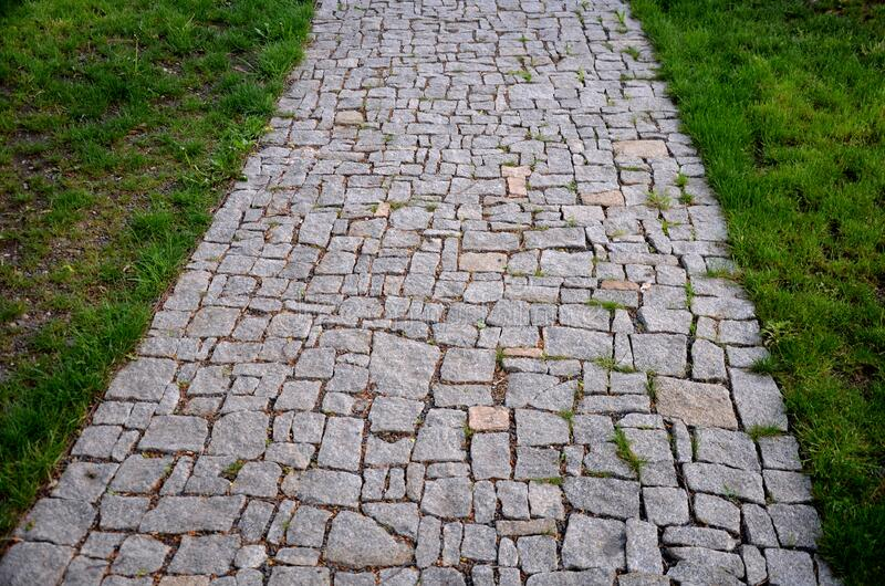 Granite paving of irregular sections of chipped stone around a park with green lawn gray color of the pedestrian path. Stone, road, cobblestone, path, pavement royalty free stock photography