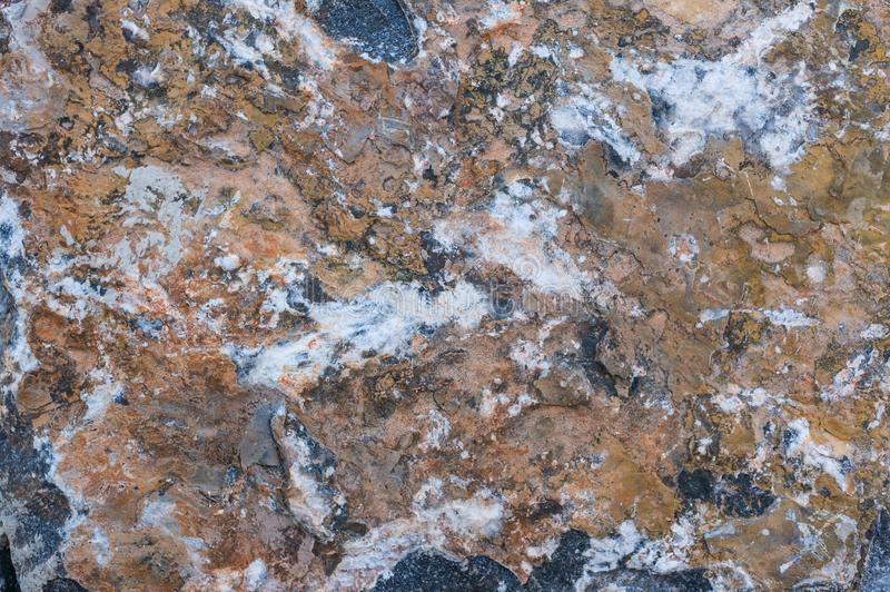Gray granite texture of the wall with brown paint and peeling plaster royalty free stock images