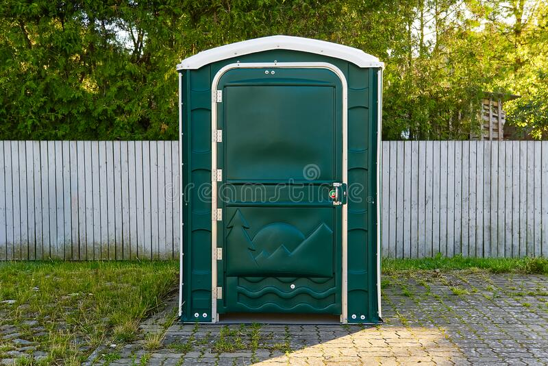 A Green Portable Plastic Toilet in a Park for events. A Green Portable Plastic Toilet in a Park for events stock image