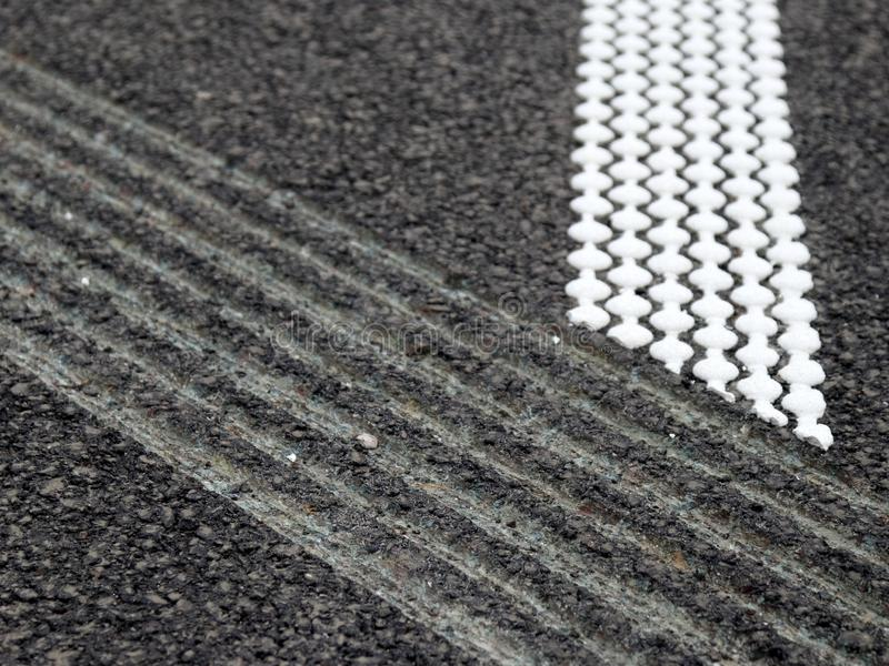Grouting and hot plastic stripe on asphalt_1. White hot platic stripe on asphalt road stock photography