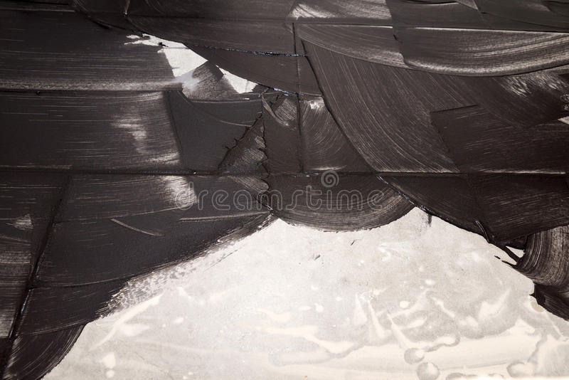 Grouting of light tiles with black grout as background. Layed bathroom tiles being grouted with black mortar as template royalty free stock photo