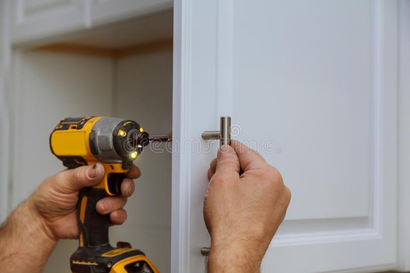 Hand on handle installation door in kitchen cabinet with a screwdriver. Hand on handle installation of door handles on opening cabinet door in kitchen with a stock image