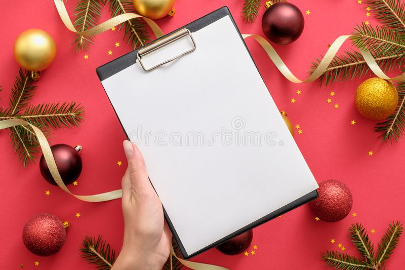 Hand holding clipboard mockup with blank paper over Christmas background with Christmas decorations, balls, gold ribbon, fir tree stock photography