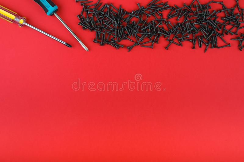 Hand screwdrivers and heap of black self-tapping screws on a red background with copy space, top view. royalty free stock photography