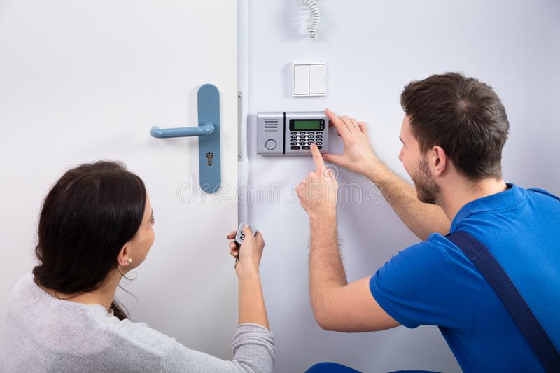 Handyman Installing Security System Near Door Wall. Close-up Of Handyman Installing Security System Near Door Wall While Woman Using Remote royalty free stock image