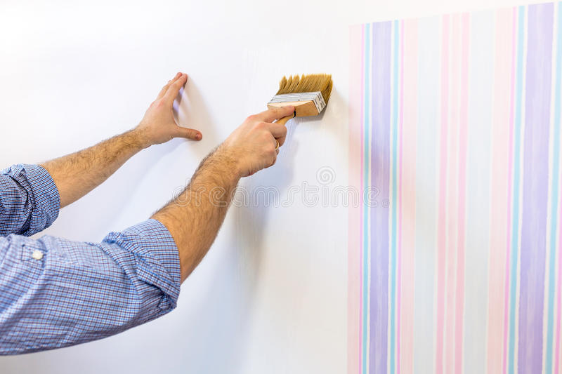 Handyman putting glue for a wallpaper stock photography