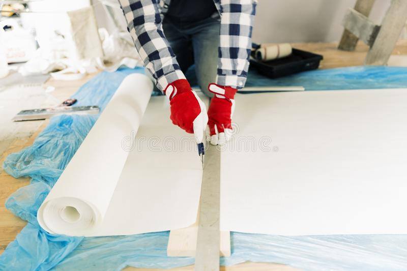 Handyman, worker measuring wallpaper to cut. Home renovation and repair concept stock images