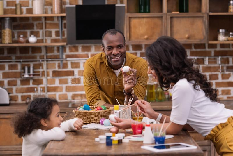 African american family painting easter eggs at kitchen. Happy african american family painting easter eggs at kitchen stock photography