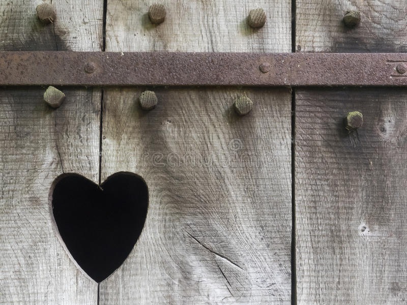 Heart carved in wood. Heart as a cutout in the wooden door of a toilet house royalty free stock photography
