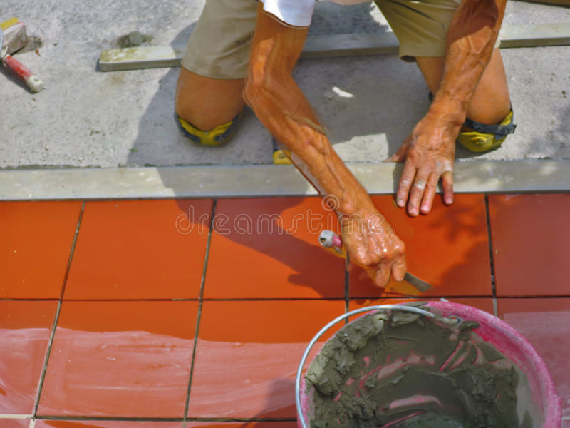 Home improvement, renovation - construction worker tiler is tiling, ceramic tile floor adhesive.  stock photography