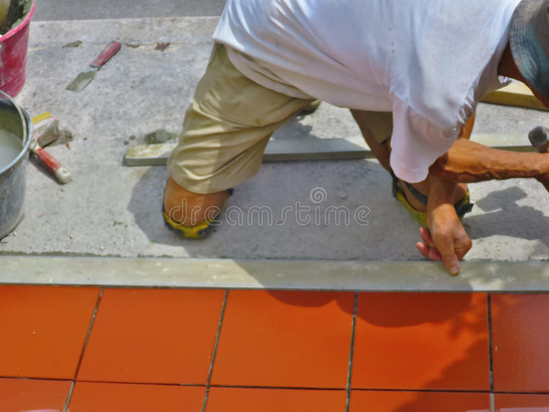Home improvement, renovation - construction worker tiler is tiling, ceramic tile floor adhesive.  stock photos