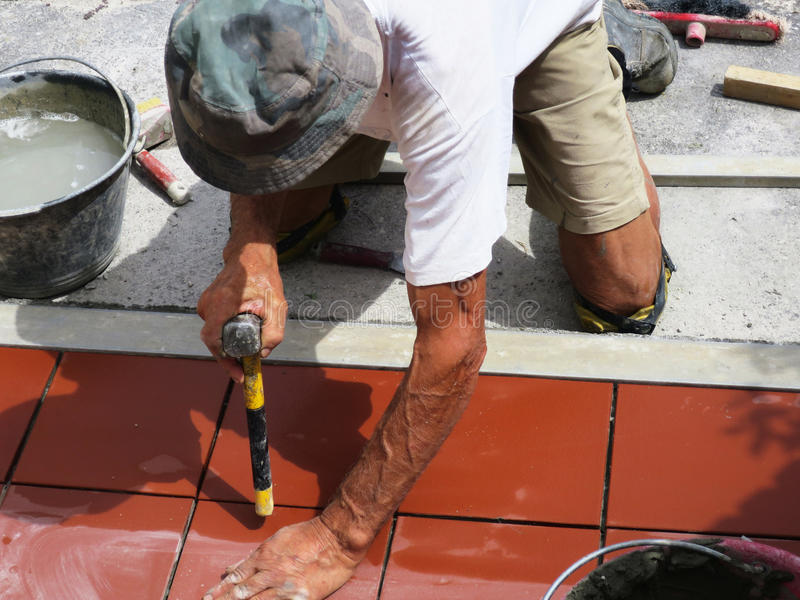 Home improvement, renovation - construction worker tiler is tiling, ceramic tile floor adhesive.  royalty free stock image