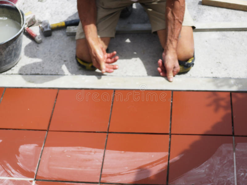 Home improvement, renovation - construction worker tiler is tiling, ceramic tile floor adhesive.  stock image