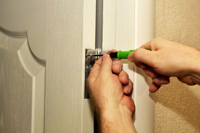 Home repair installation of door hinges in the house by the hands of a master. Using a screwdriver royalty free stock photos