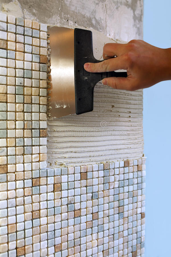 Home repair: installing the mosaic tile on the wall stock photography