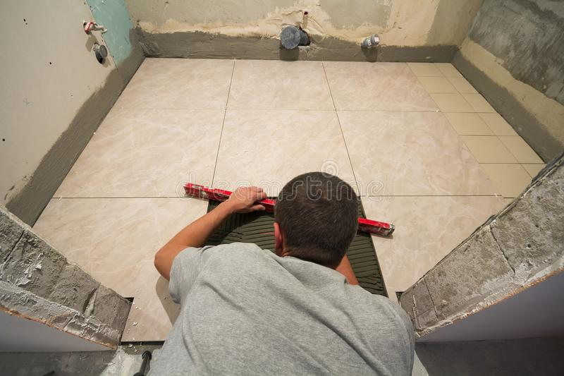 Home tiles improvement - handyman with level laying down tile floor. Renovation and construction concept. stock image