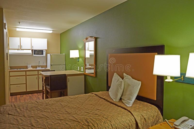 Hotel room with kitchen. Home style hotel room with bed, table and kitchen royalty free stock image