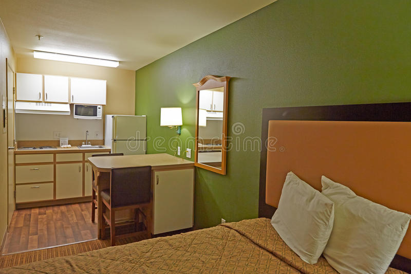 Hotel room with kitchen. Family style hotel room with bed, table and kitchen stock photos