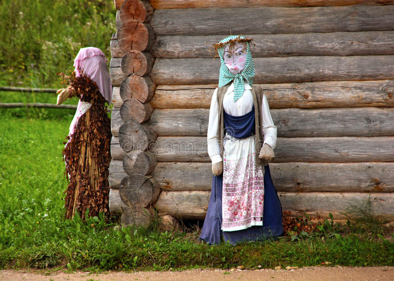 The hut in the Russian village. Scarecrow next to the hut. The hut in the Russian village/ Mikhailovskoe, Pskov royalty free stock photos