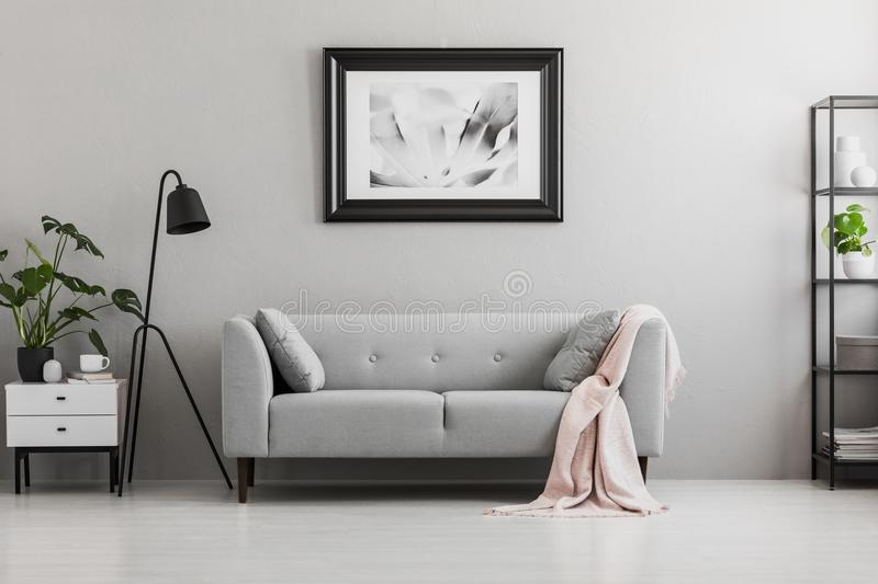 Industrial black floor lamp and a pink blanket on an elegant settee with cushions in a gray living room interior with place for a stock photo