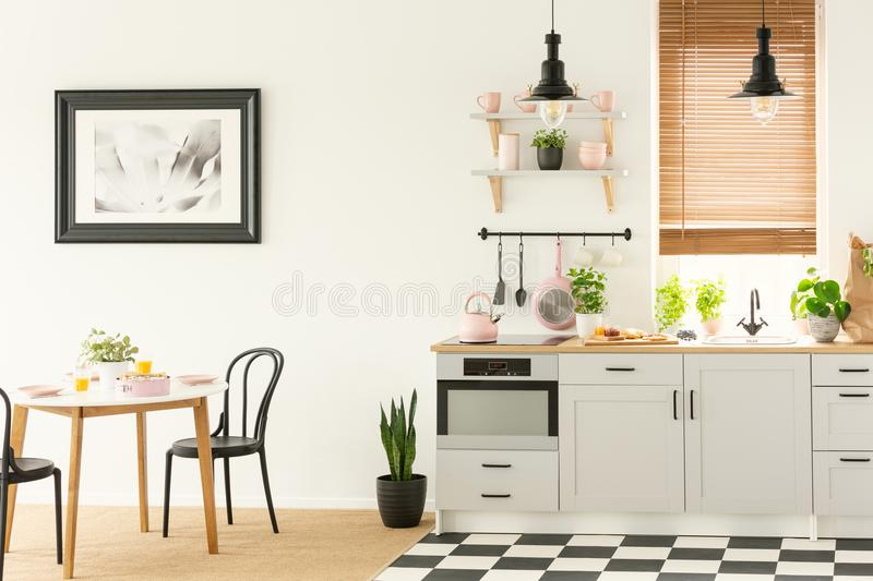 Industrial lamps and black dining chairs in a white kitchen interior with a modern oven and breakfast food. Concept photo stock photo