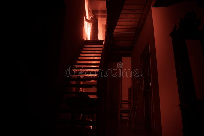 Inside of old creepy abandoned mansion. Silhouette of horror ghost standing on castle stairs to the basement. Spooky dungeon stone. Stairs in old castle with stock images