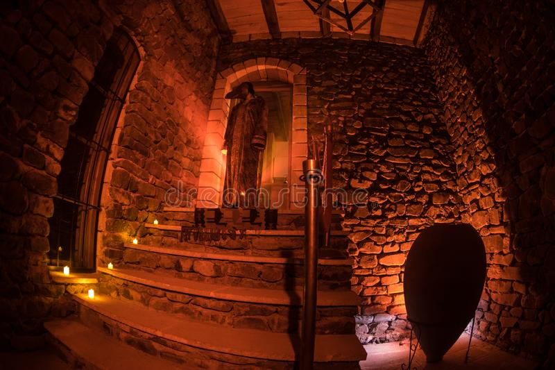 Inside of old creepy abandoned mansion. Staircase and colonnade. Silhouette of horror ghost standing on castle stairs to the basem. Inside of old creepy stock photography