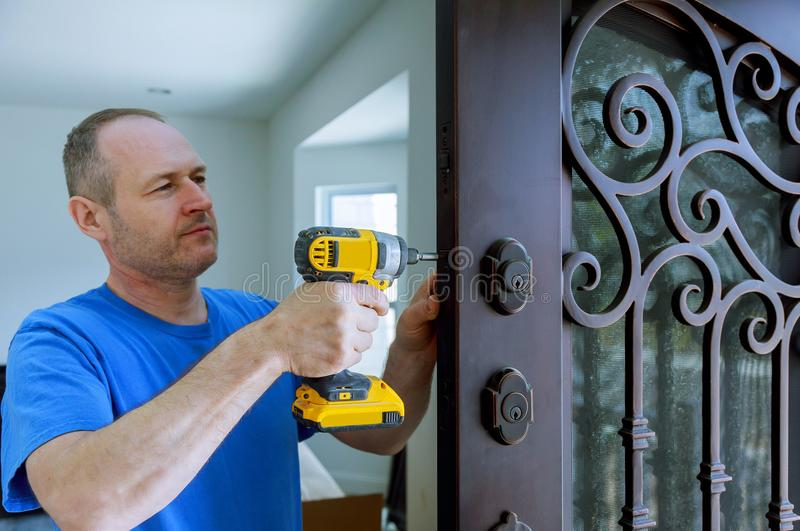 Installation of interior with a lock in the door leaf using an drill screwdriver,for holding screws. Close-up royalty free stock photo
