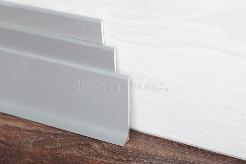 Installed skirting on the a wooden wall royalty free stock photography