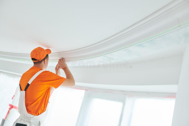 Installing decorative ceiling molding. home repair and decoration stock photos