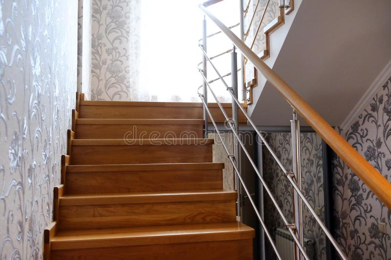 Interfloor stairs from the valuable breeds of wood for the cottage. Wooden staircase to the second floor. Modern wooden staircase. With brown wooden railing royalty free stock photo
