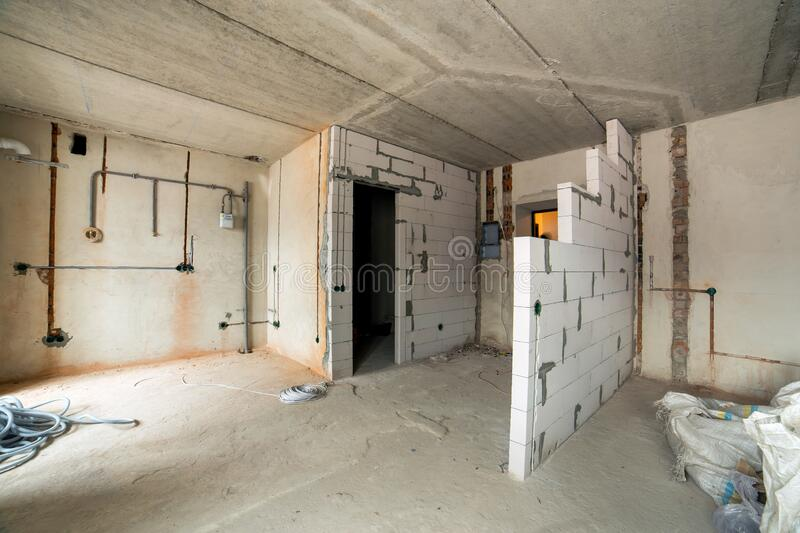 Interior of an apartment room with bare walls and ceiling under construction.  royalty free stock image