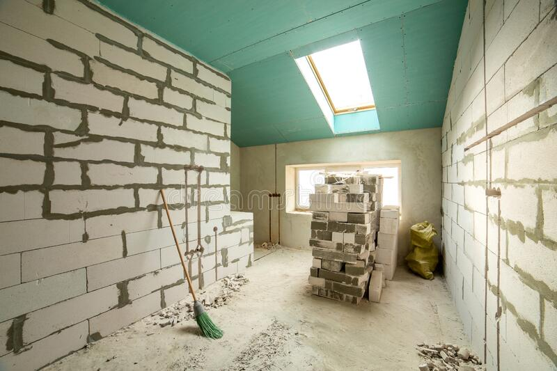Interior of an apartment room with bare walls and ceiling under construction.  stock photo