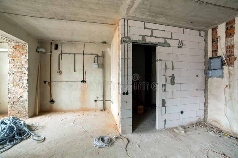 Interior of an apartment room with bare walls and ceiling under construction.  stock photography