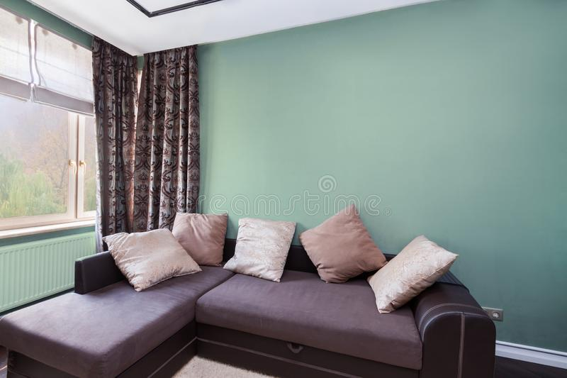 Interior design with dark relax sofa and colorful cushions window curtains and olive color wall stock photo