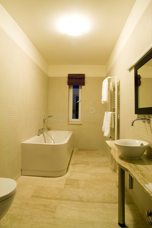 Interiors of a bathroom. A shot of the interiors of a modern and minimalist bathroom. Colour scheme is white and beige. Picture includes a bath tub, sink, mirror stock photography