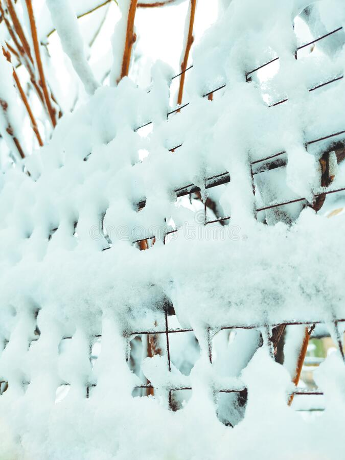 Iron net fence covered snow. Metal rusty fence-mesh netting in the snow. Close-up shot of snow on a fence. Lattice fence covered. With fresh snow. White stock photography