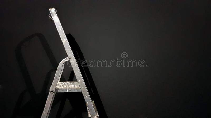 Iron step ladder against a gray wall. Preparing for home repairs. Old and dirty aluminum in an empty room, shadow. White gray stock image