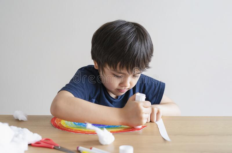 Kid putting glue stick on paper for sticking cotton wool as decorative elements for clouds on rainbow. Child Boy enjoy art stock photo